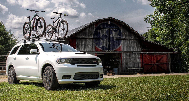 Mostrar Dodge Durango con dos bicicletas en la parrilla portaequipaje frente a un establo. Sujeta adecuadamente toda la carga.