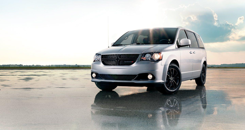 Se muestra una vista frontal de medio perfil de una Dodge Grand Caravan 2020 sobre asfalto húmedo.