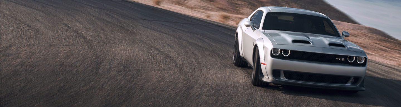 Vista frontal de medio perfil de un Dodge Challenger en una pista de carreras.