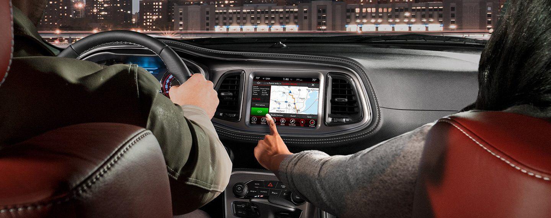 El pasajero delantero en unDodge Challenger2021 se acerca a la pantalla táctil del vehículo, donde se muestra un mapa de ruta.